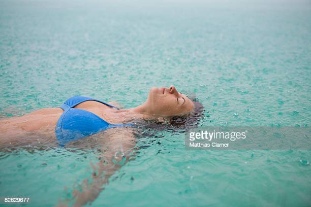 young woman floats in lagoon while it rains