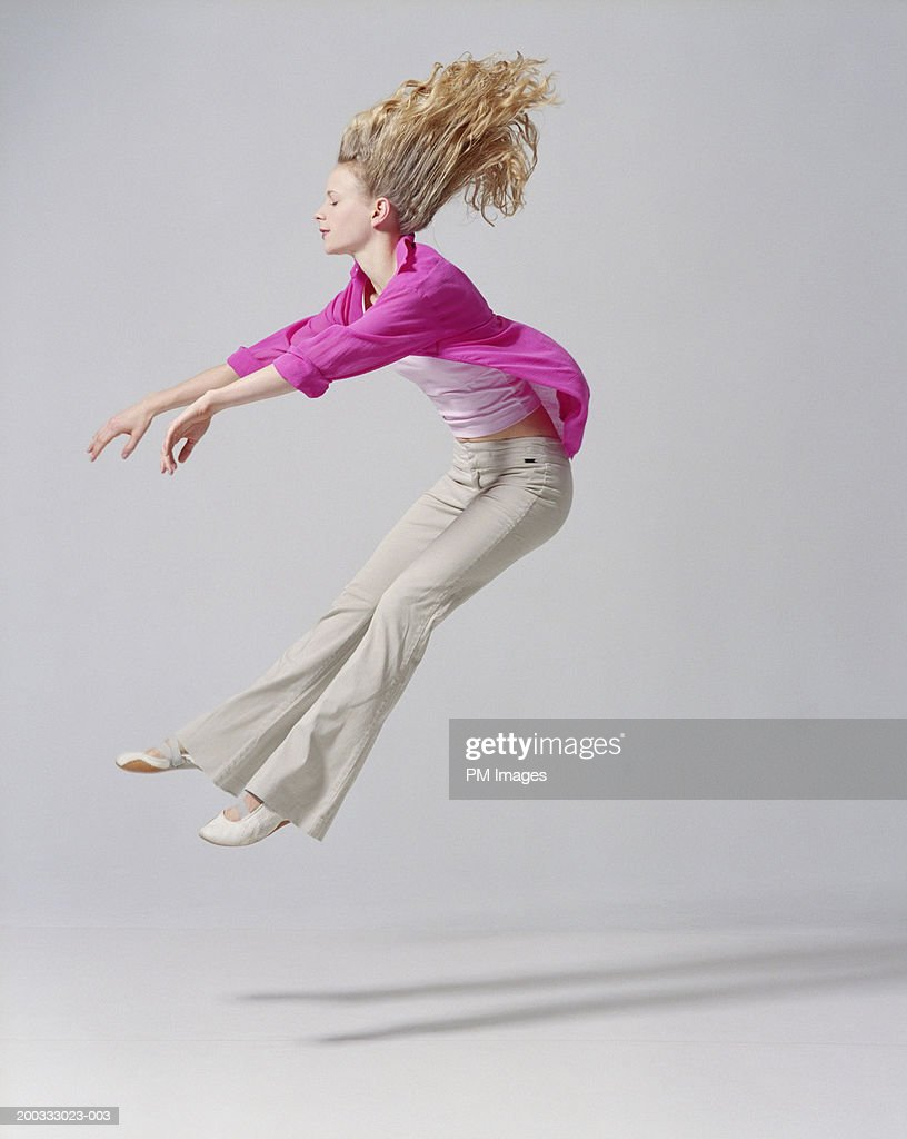 Young woman flying backwards, arms extended, side view : Stock Photo
