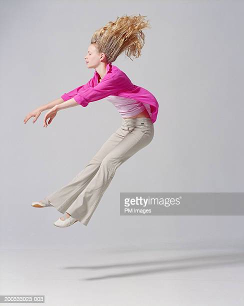 young woman flying backwards, arms extended, side view - trousers stock pictures, royalty-free photos & images