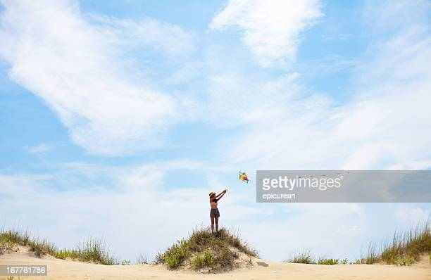 Young woman flying kite on summery day at the beach