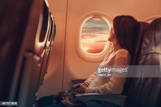 young woman flying to france - plane stock photos and pictures