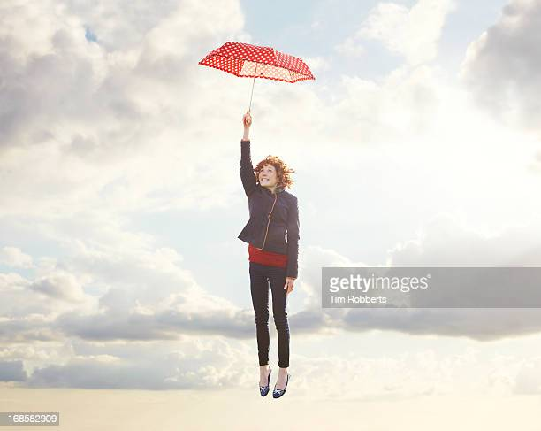 young woman flying with umbrella. - dreamlike stock pictures, royalty-free photos & images