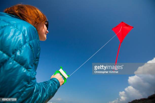 A young woman flys a red kite in the sky while at an Oregon Coast Beach.