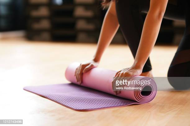 young woman folding yoga mat  after class end - yoga stock pictures, royalty-free photos & images