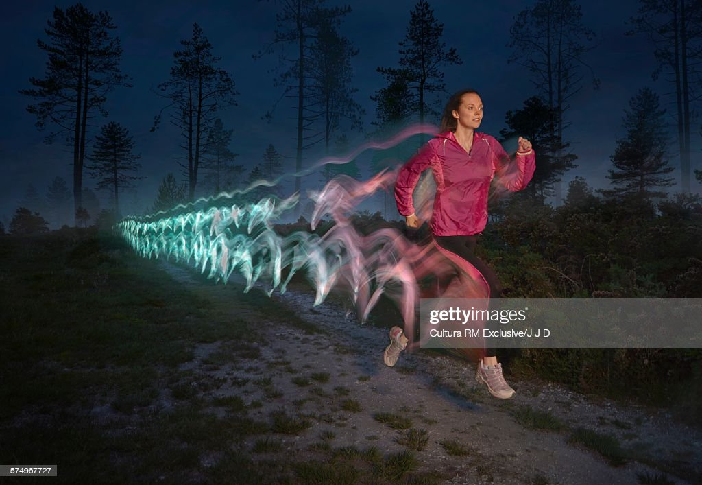 Young woman followed by light trails running on forest dirt track at night : Stock Photo
