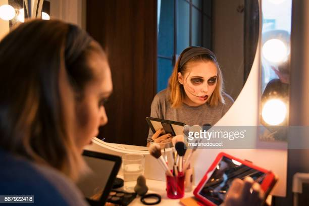 young woman following a makeup tutorial on social media at home - stage make up stock pictures, royalty-free photos & images