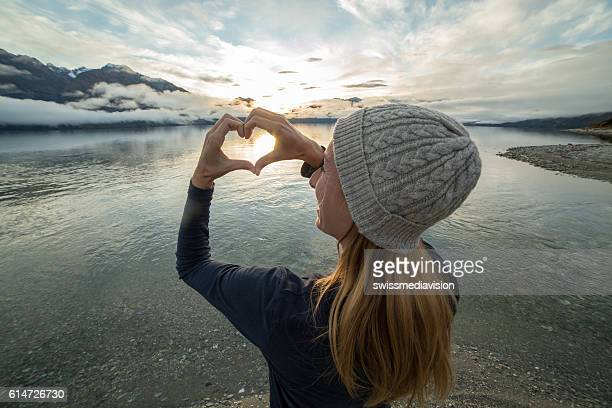Young woman frames beautiful landscape into heart shape