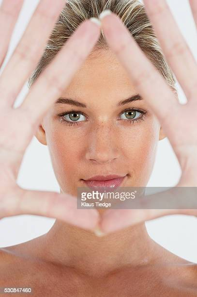 Young woman framing face with her hands