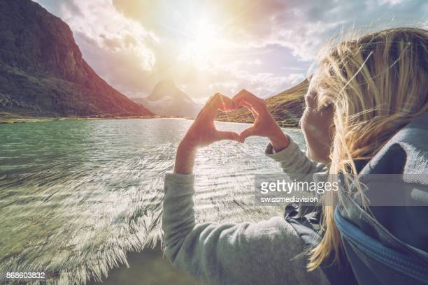 young woman framing matterhorn with heart shape, switzerland - pinnacle peak stock pictures, royalty-free photos & images