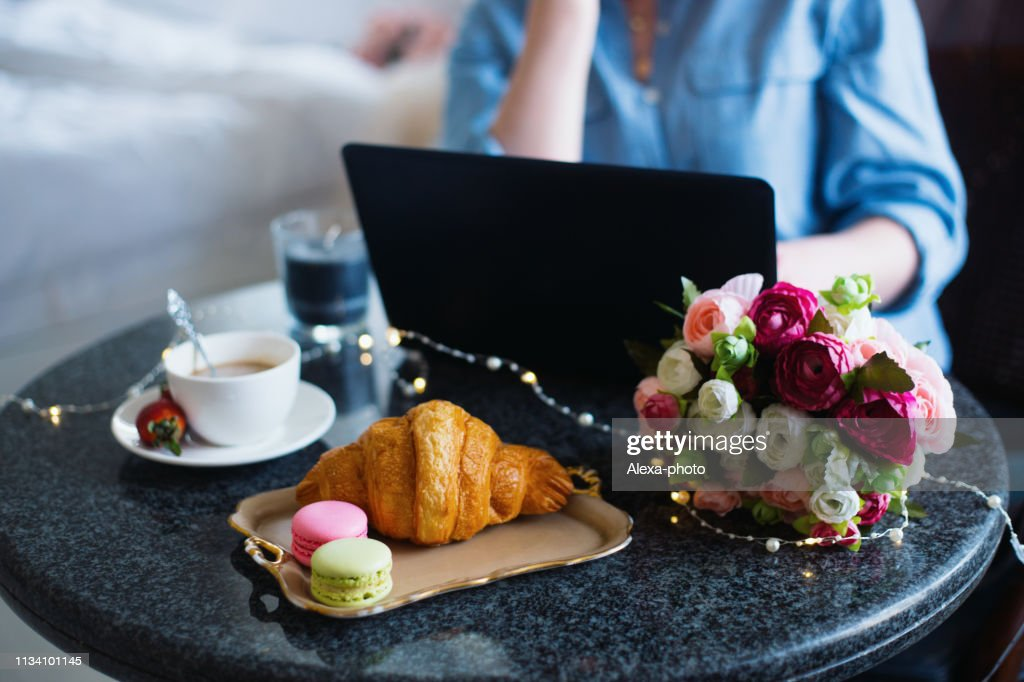 Young woman freelancer in blue shirt working on laptop during lunch with coffee, croissant, macaroons and flowers on table : Stock Photo