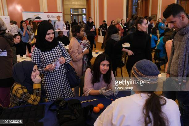 A young woman from Afghanistan tries out the gloves with a mild electric current that are meant to simulate the effect of Parkinson's disease at a...