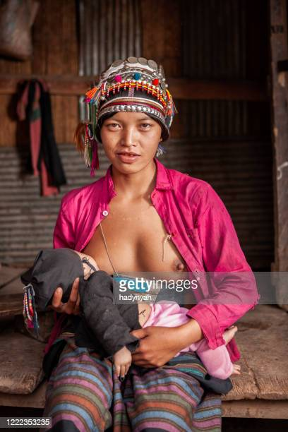 young woman from akha hill tribe breastfeeding her baby - laotian culture stock pictures, royalty-free photos & images
