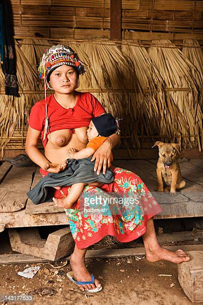 young woman from akha hill tribe breastfeeding her baby - woman breastfeeding animals stock photos and pictures