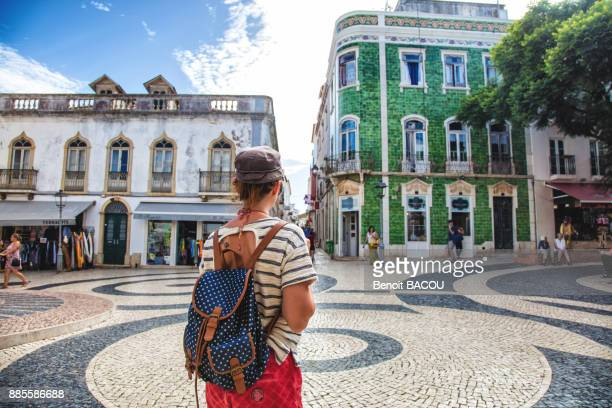 young woman from behind, observed the square of the town of burgau, algarve region, portugal - algarve stock photos and pictures