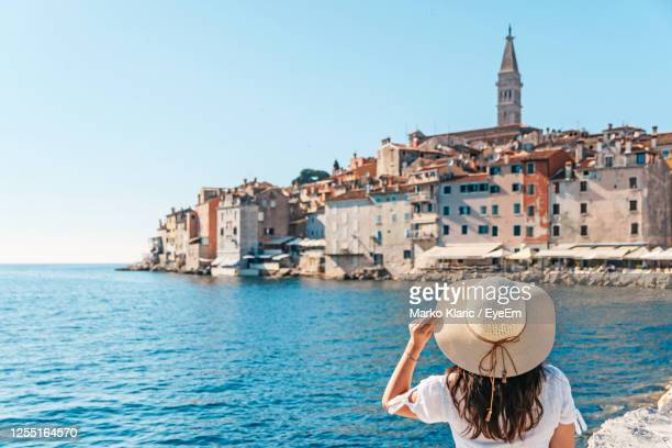 young woman from behind. picturesque old town by sea in background. - croacia fotografías e imágenes de stock