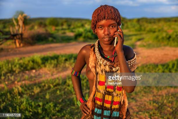 young woman from hamer using smart phone, omo valley, ethiopia, africa - hamer tribe stock pictures, royalty-free photos & images