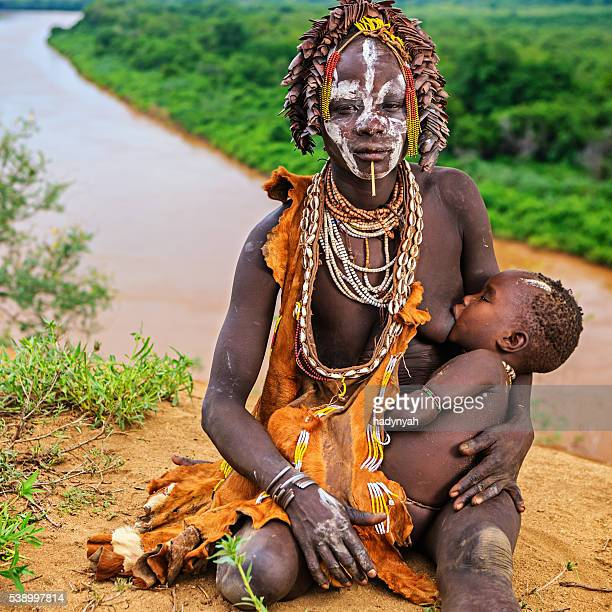 Young woman from Karo tribe breastfeeding her baby, Ethiopia, Africa