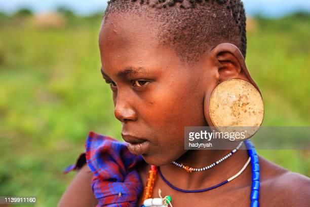 jovencita de la tribu mursi, etiopía, áfrica - tribu mursi fotografías e imágenes de stock