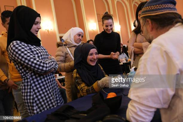 A young woman from Syria reacts to a mild electric current in the gloves she is wearing that is meant to simulate the effect of Parkinson's disease...