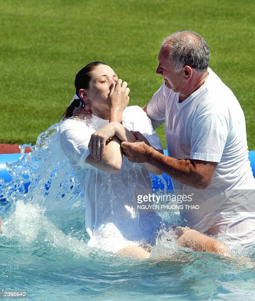 A young woman from the Jehovah's Witnesses is baptized on July 20 2003 at the Prague Stadium of Eugeune Rosicki in a pool of water along with...