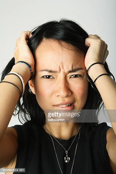 Young woman frowning, biting lips, hands on head, portrait, close-up