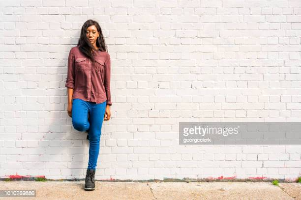 young woman - full length portrait - brick wall stock pictures, royalty-free photos & images