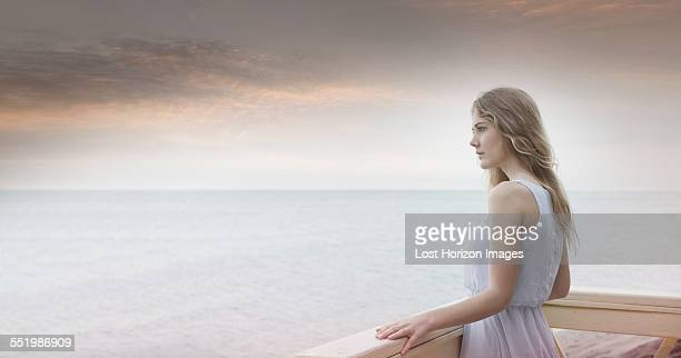 Young woman gazing out to sea from balcony, Miami Beach, Florida, USA