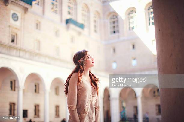 Young woman gazing up in historic courtyard