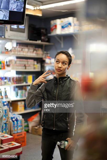 young woman gesturing - convenience store stock photos and pictures