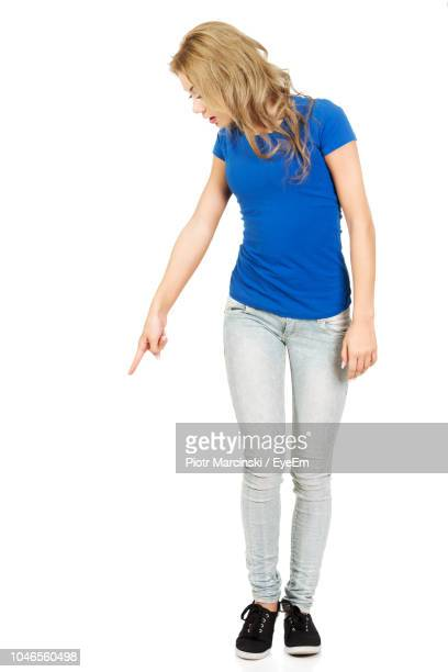 young woman gesturing while standing against white background - guardare verso il basso foto e immagini stock