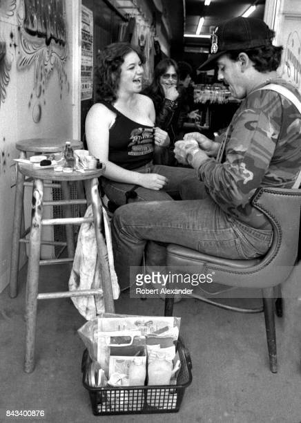 A young woman gets a temporary tattoo in Daytona Beach Florida during the city's 1983 Bike Week The annual motorcycle event and rally has attracted...