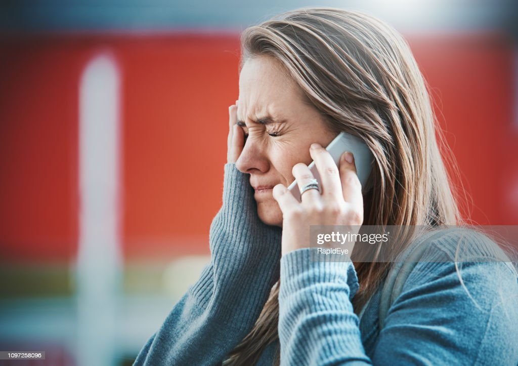 Young woman gets bad news on her mobile phone : Stock Photo