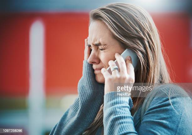 young woman gets bad news on her mobile phone - distraught stock pictures, royalty-free photos & images