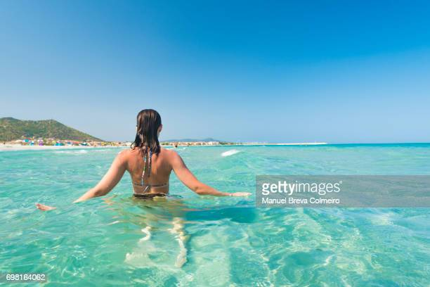 Young woman gets into the sea