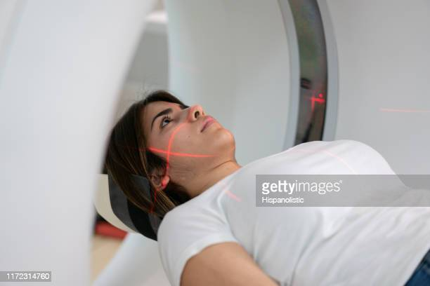 young woman getting a brain scan at the mri machine in hospital - pet scan machine stock pictures, royalty-free photos & images