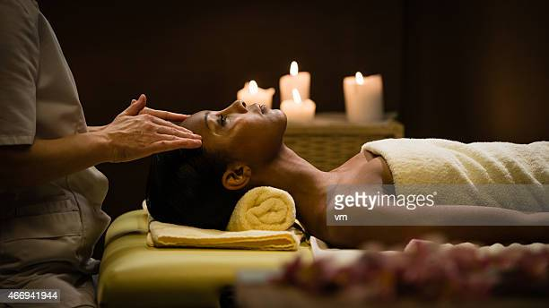young woman getting a head massage in a relaxing environment - black massage therapist stock photos and pictures