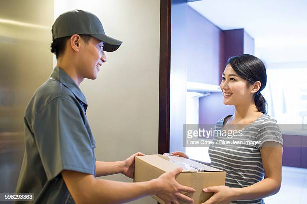Young woman getting a package from delivery person