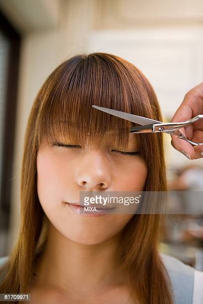 Young woman getting bangs cut