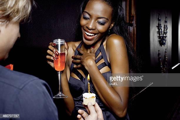 Young woman getting birthday cake in nightclub