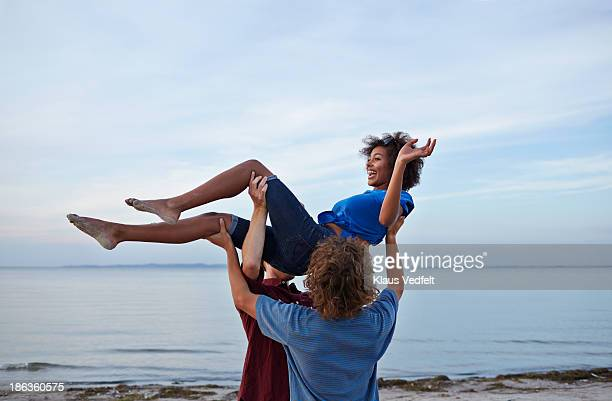 young woman getting carried by two teen boys - picking up stock pictures, royalty-free photos & images