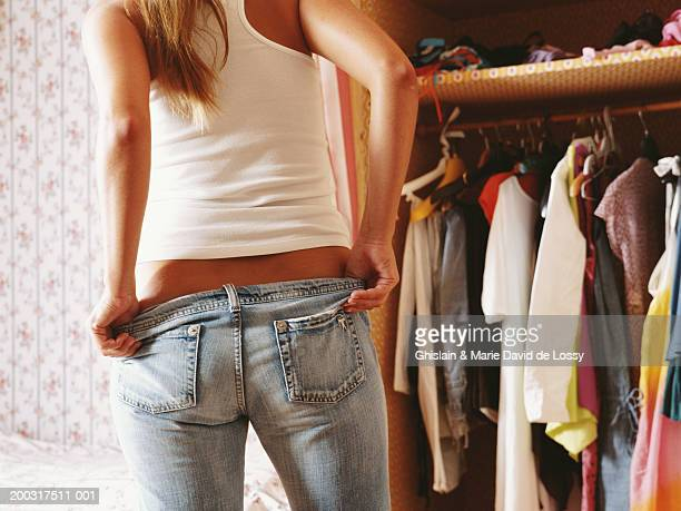Young woman getting dressed in bedroom, pulling up jeans, rear view