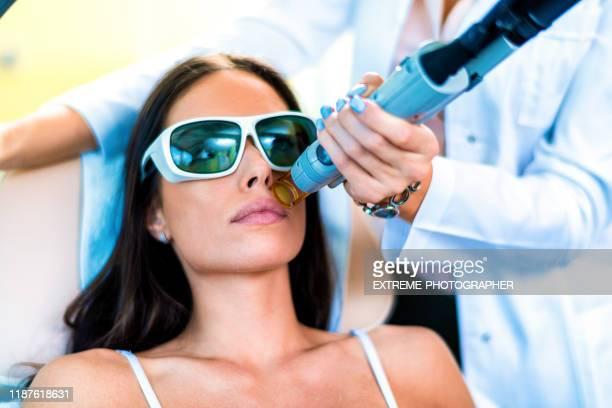 eine junge frau bekommt gesichtsbehaarung durch einen laser-depilator in einem kosmetikzentrum entfernt - behaart stock-fotos und bilder