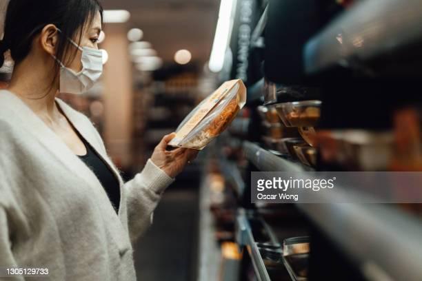 young woman getting food from cooling shelf in supermarket - aufwärmen stock-fotos und bilder