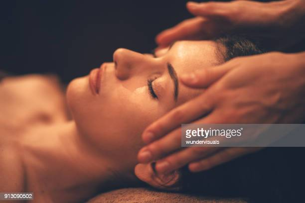 young woman getting head massage at day spa salon - massaggi foto e immagini stock
