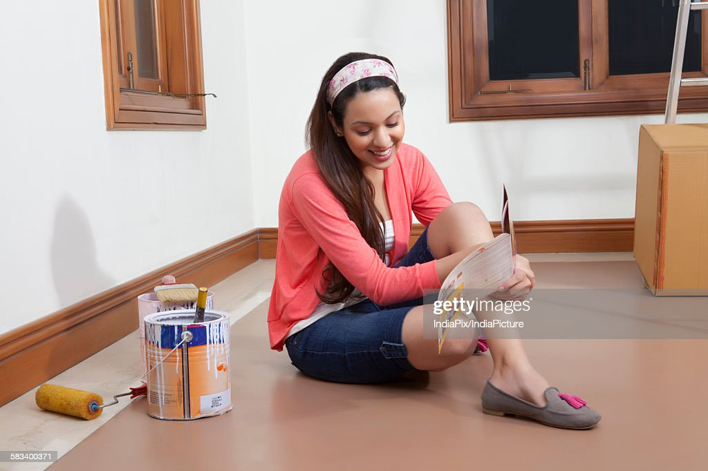 Young woman getting her house painted : Stock Photo
