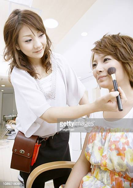 A young woman getting her makeup done
