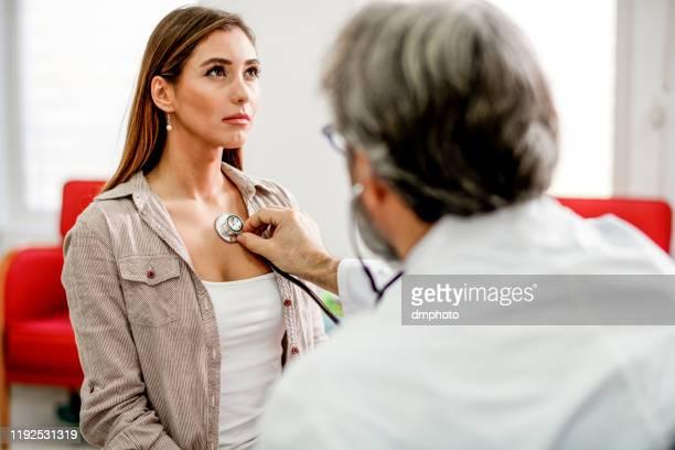 giovane donna farsi esaminare il petto doloroso da un medico. - visita foto e immagini stock
