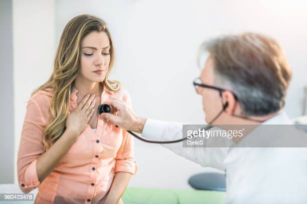 young woman getting her painful chest examined by a doctor. - asthmatic stock photos and pictures