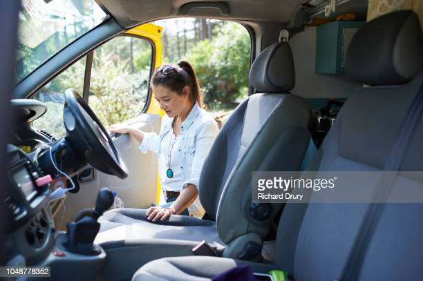 Young woman getting into the drivers seat of her camper van