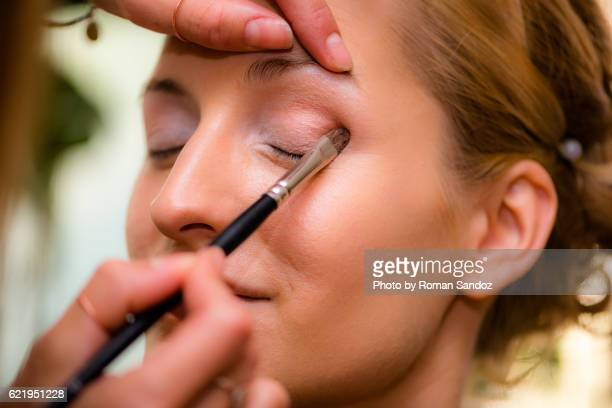 Young woman getting make-up done